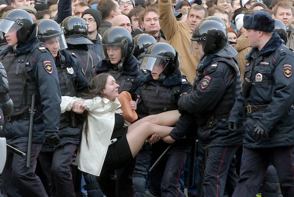 Džentlmenští policisté přenášejí mladou ženu přes velkou kaluž, aby si nezašpinila oblečení.